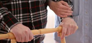 Auttaja pitää rollaattoria työntävää vanhusta kädestä
