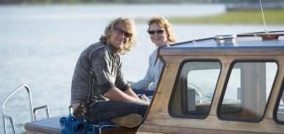 Iloisia ihmisiä veneen kannella kesäpäivänä