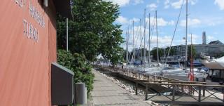 Vierasvenesataman seinä ja kuva laiturista, jossa veneitä kiinni.