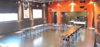 Sali, jossa kokousasetelmassa pöydät ja tuolit.
