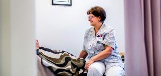 Hoitaja istuu potilan pedillä