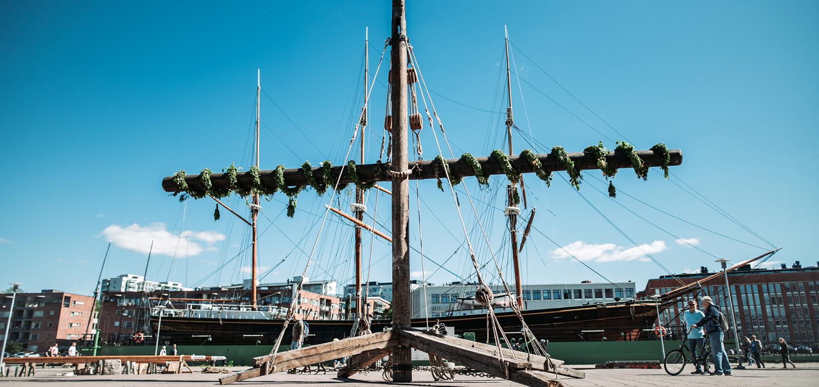 Museolaiva Sigynin vanhoista mastoista rakennettu taideteos, taustalla museolaiva Sigyn Aurajoessa