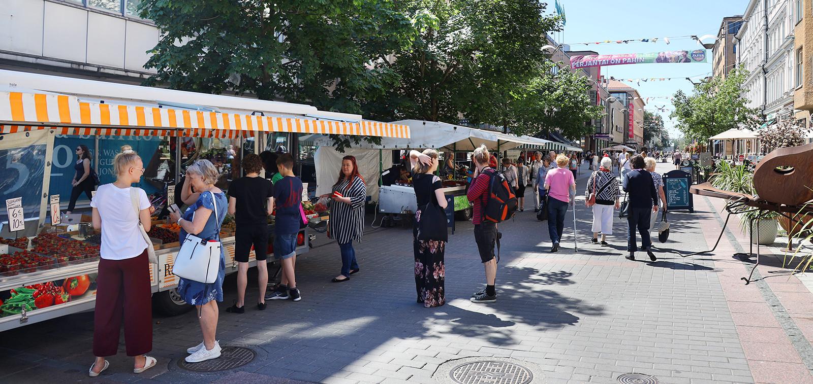 Torikojuja ja ihmisiä kesäisellä kävelykadulla.