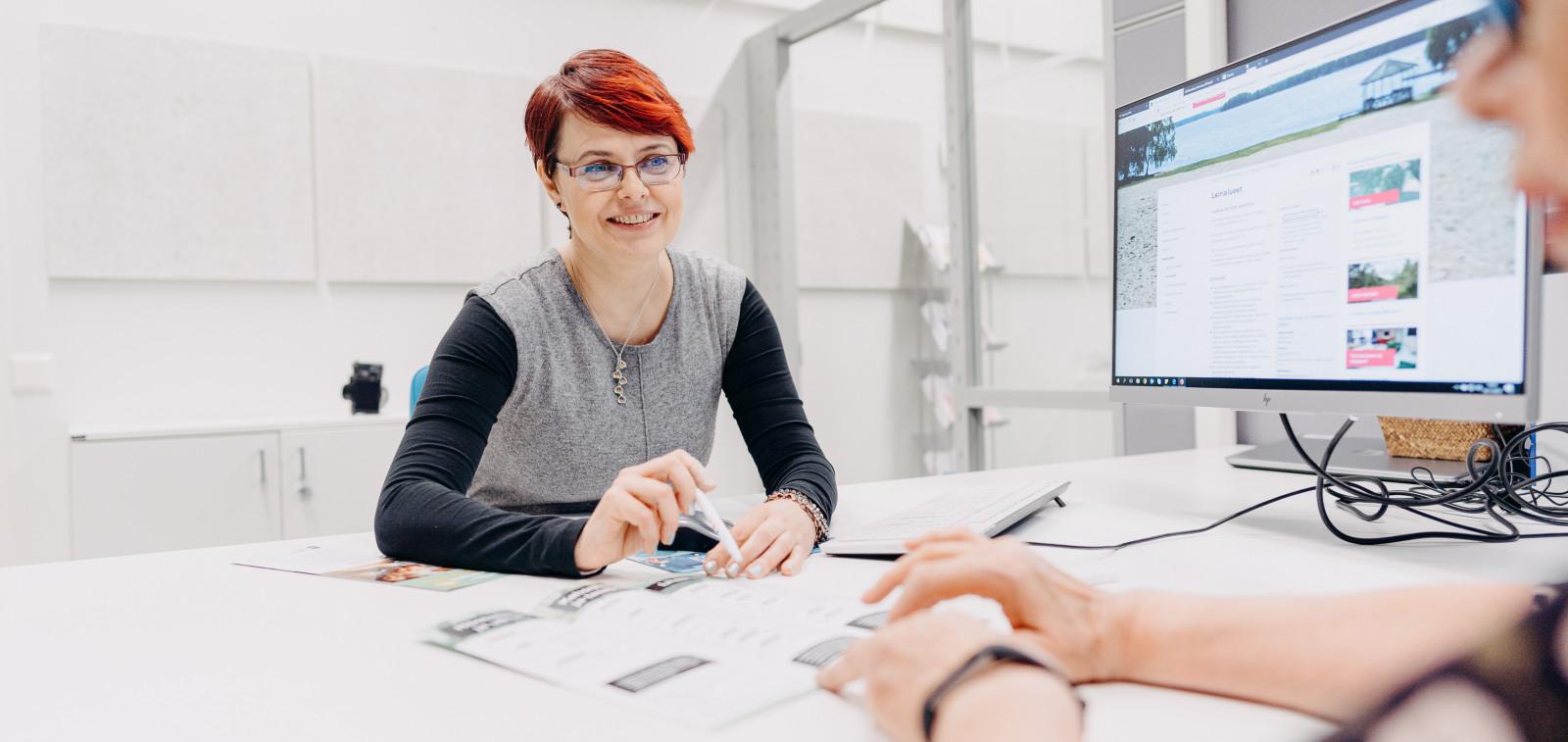 Nuorisopalveluiden asiakaspalvelija Ann-Mari Hammarberg palvelemassa asiakasta Kauppatorin Monitorissa.
