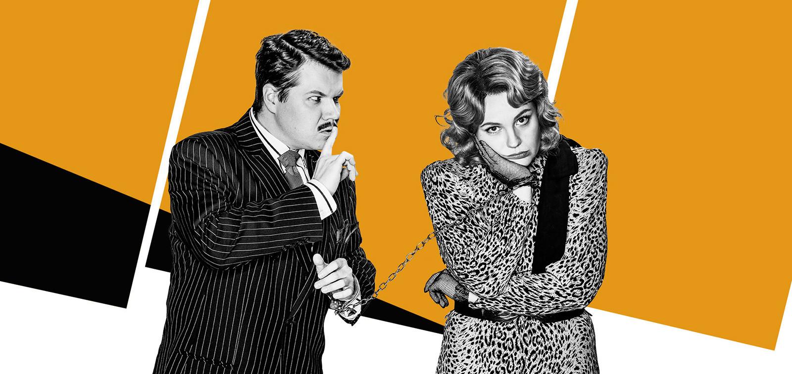 Mainoskuvassa mies ja naisnäyttelijä käsiraudoilla toisiinsa kahlittuna