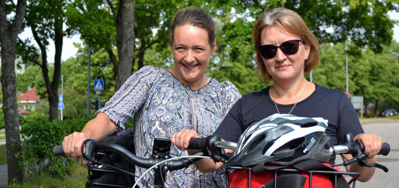 Kaksi naista taluttamassa sähköpyöriä kesällä