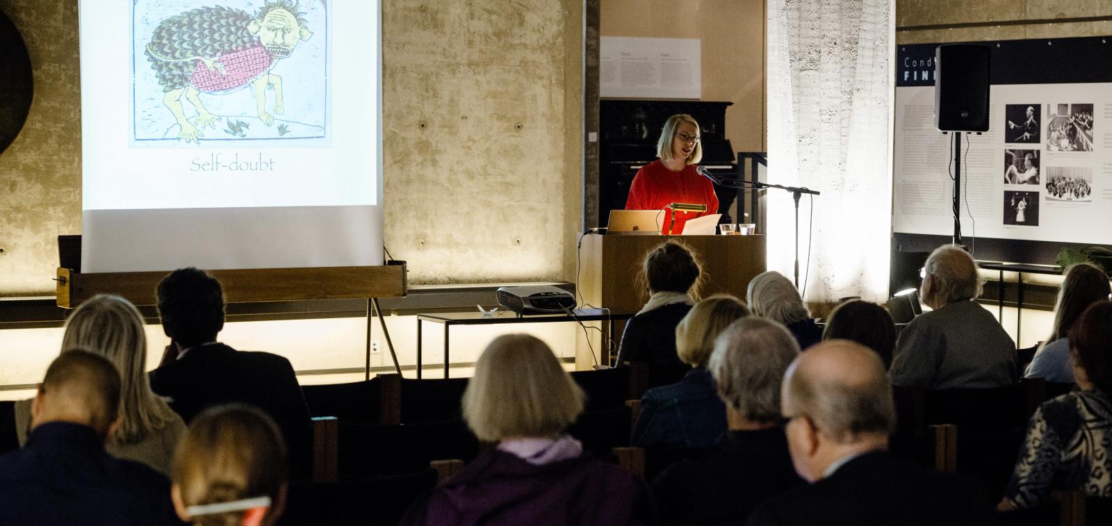 """Luentosalissa nainen luennoi ja ihmiset kuuntelevat istuen. Taululle on heijastettu kuva oliosta ja sen alla on teksti """"self-doubt"""""""