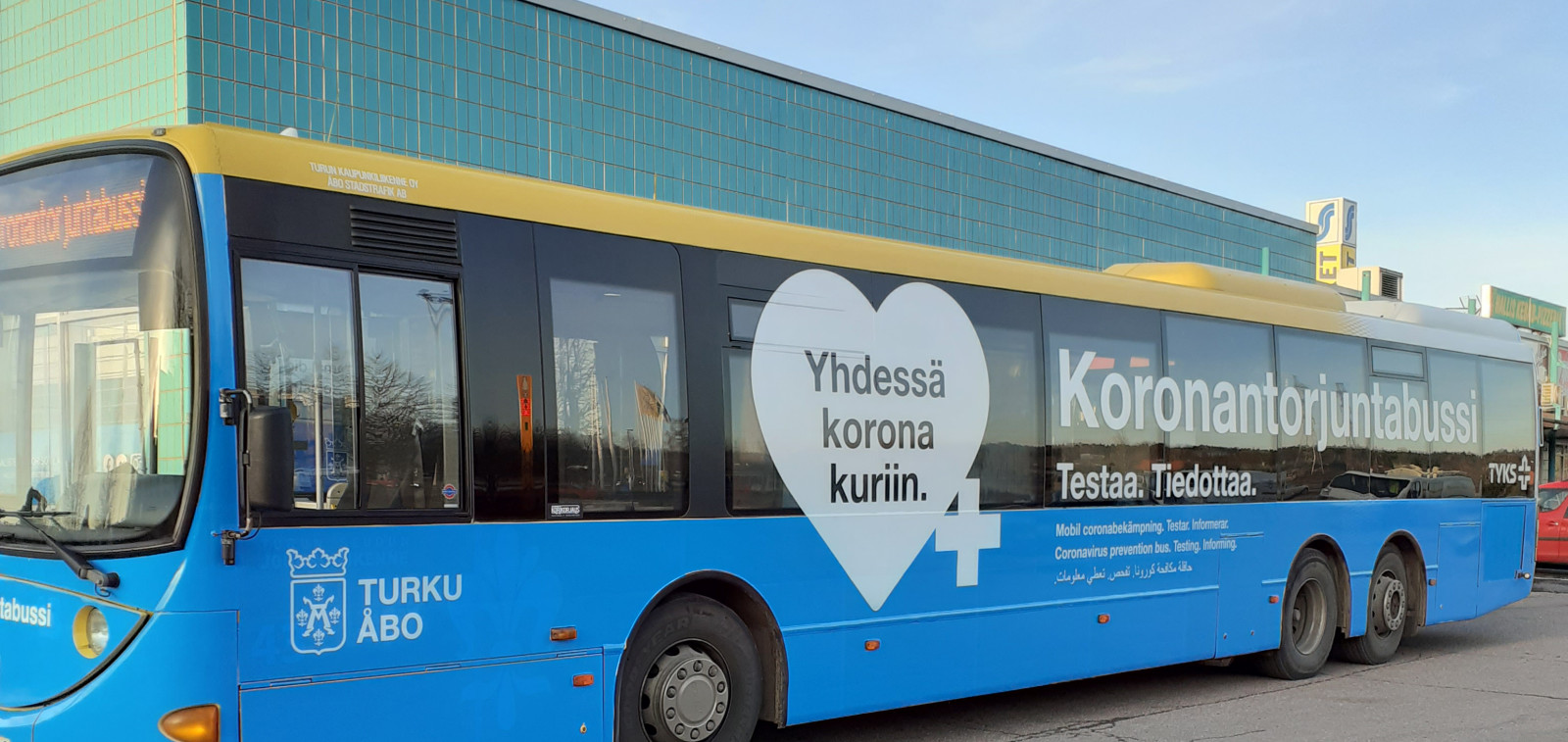 Sininen Turun logoilla varustettu linja-auto on pysäköity rakennuksen edustalle.