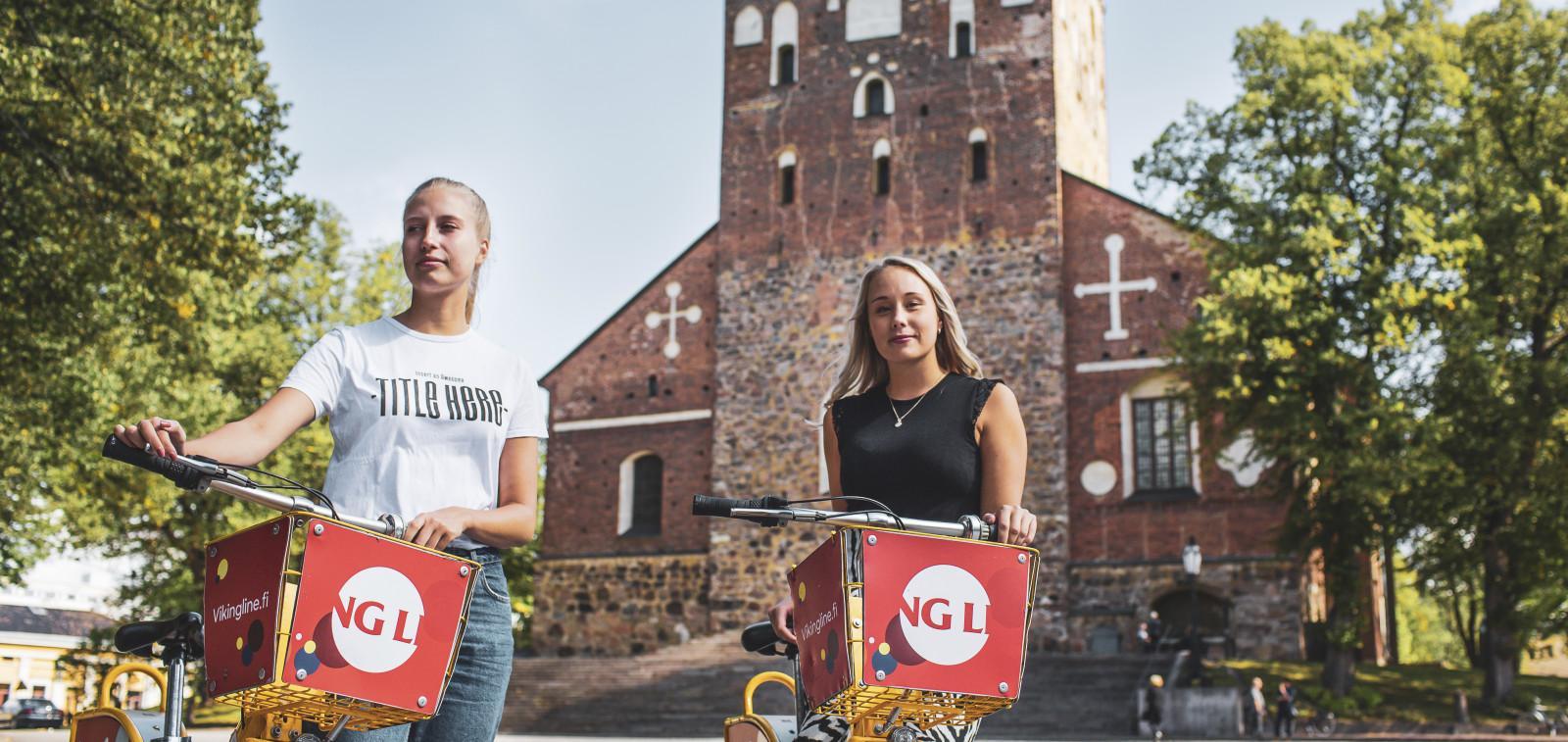 Kaksi vaaleaa naista Tuomiokirkon edessä taluttamassa Föli-fillareita