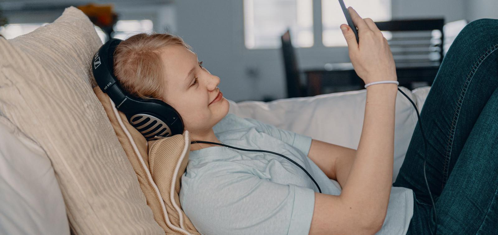 Digituen kuvituskuva, Digi- ja väestötietovirasto. Kuvassa tyttö istuu sohvalla ja käyttää kännykkää kuulokkeet korvilla.