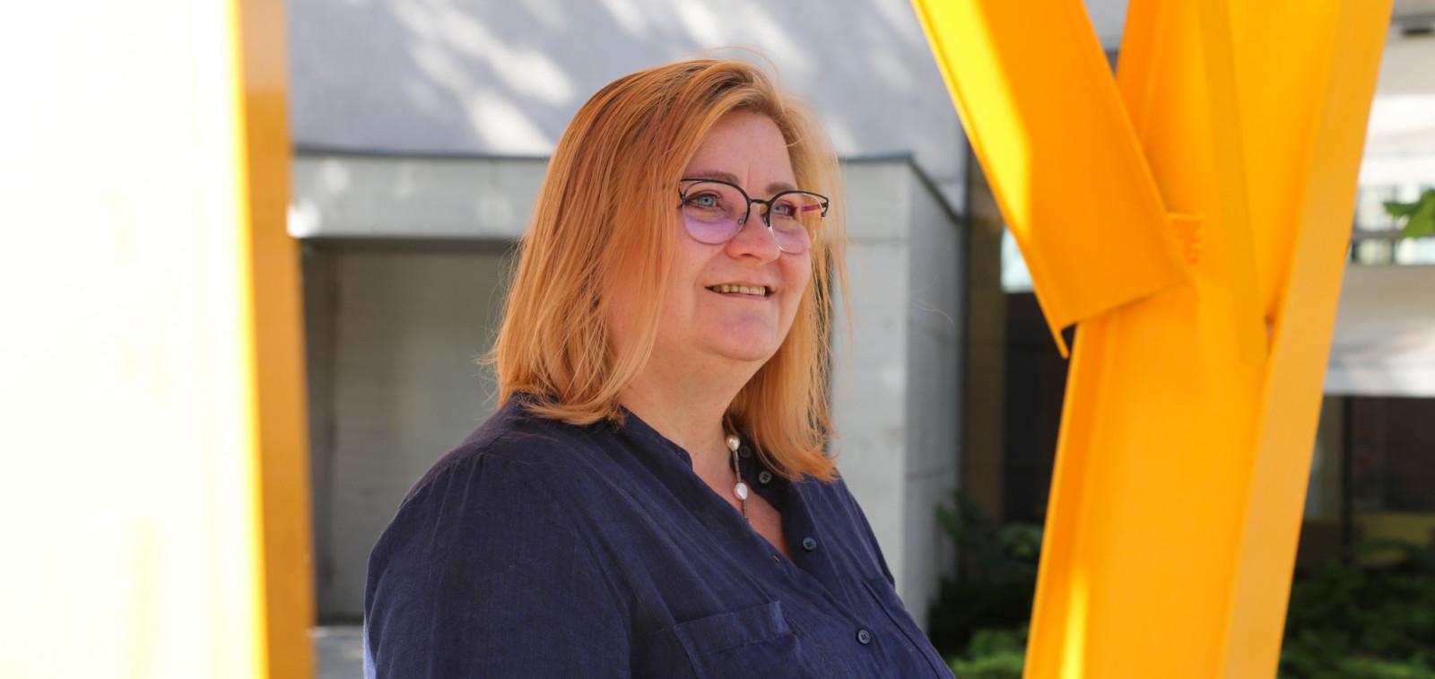 Eevastiina Rindell seisoo Turun kaupunginkirjaston sisäpihan vasikkaveistoksen keltaisten rakennelmien keskellä. Hänellä on puolipitkät punertavat hiukset, silmälasit ja tummansininen paita päällään.