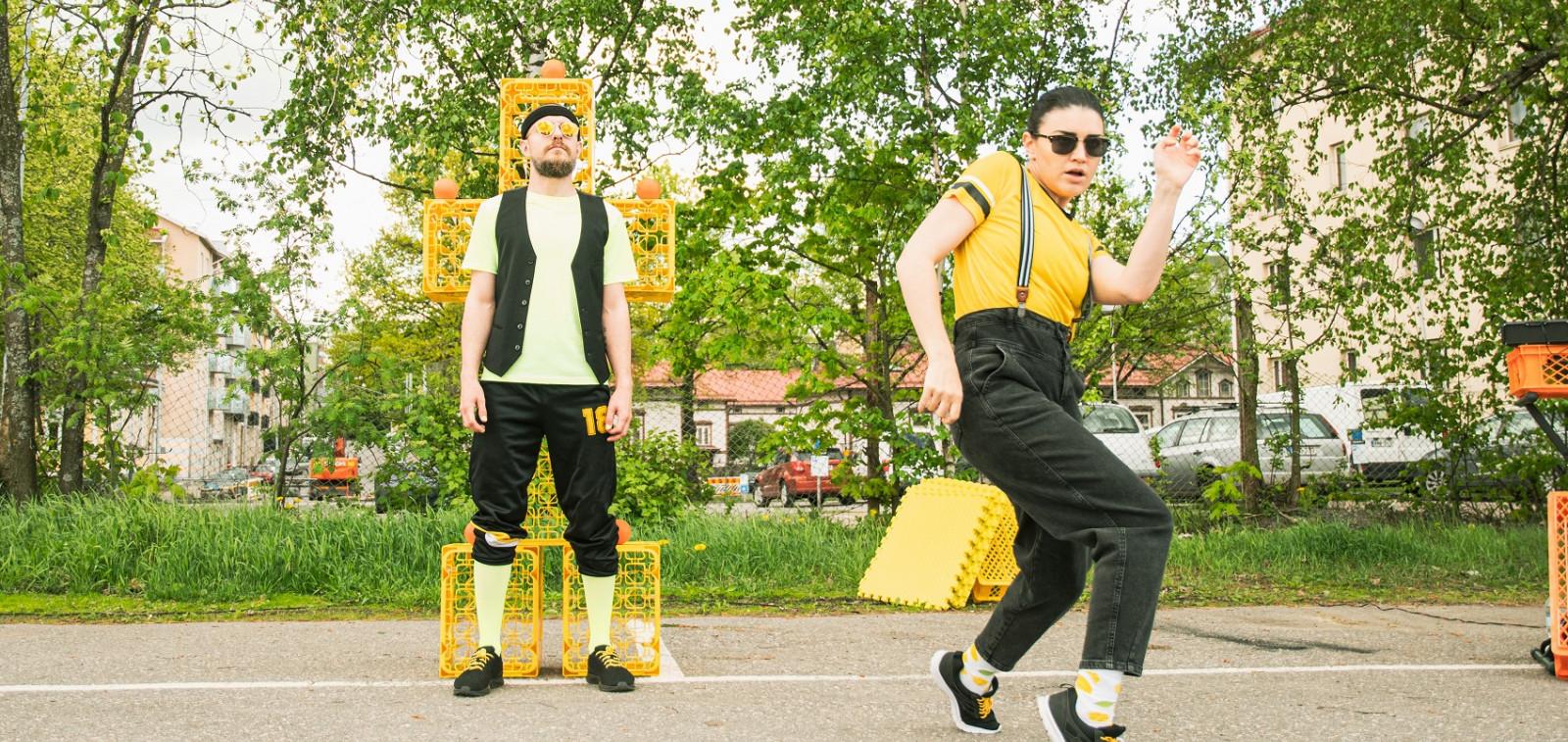 Kaksi sirkustaitelijaa keltamustissa vaatteissa