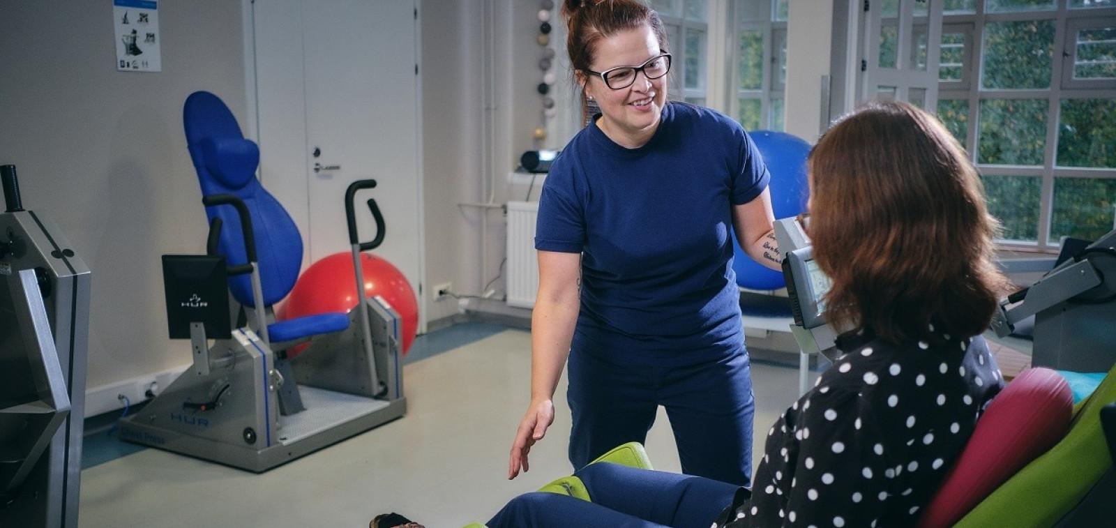 Fysioterapeutti kuntouttaa asiakasta kuntosalilla