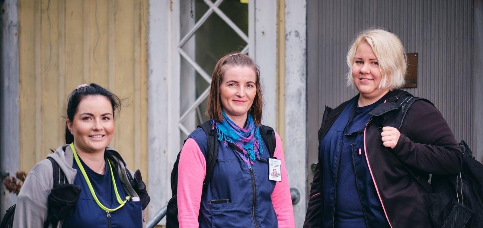 Kotihoidon kolme työntekijää seisovat portailla rivissä ulkona