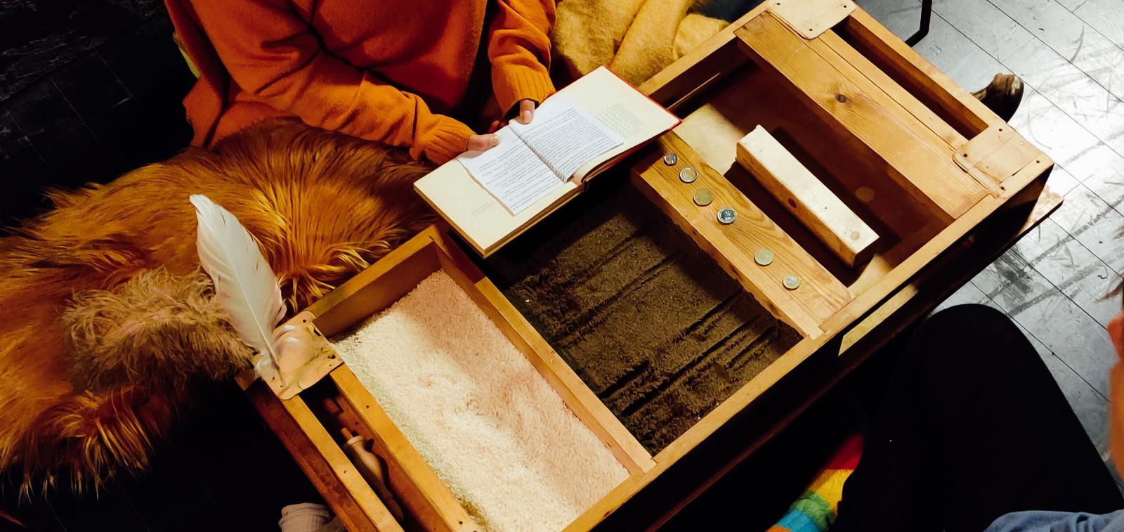 Kaksi ihmistä puusta tehdyn pelin ääressä. Toinen lukee kirjaa. Pelin päällä on kolikoita.äliseen jännitteeseen perustuva pelillinen alkusysäys taloon.