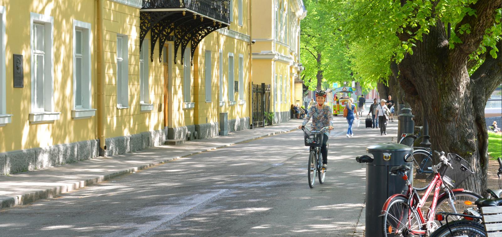 Pyöräilijä jokirannassa