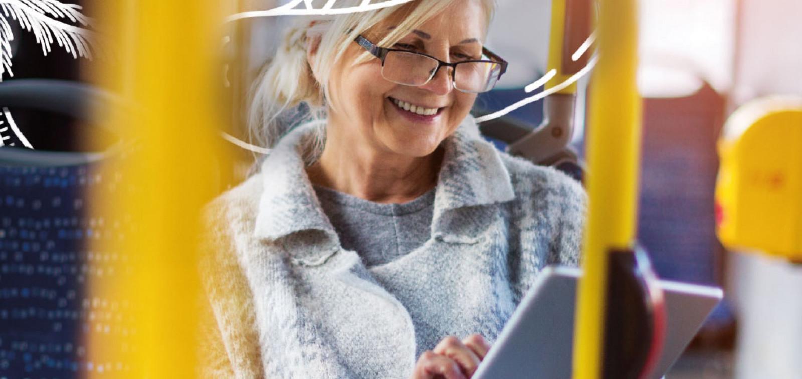 Nainen bussissa hattu päässä täyttämässä kyselyä iPadilla.