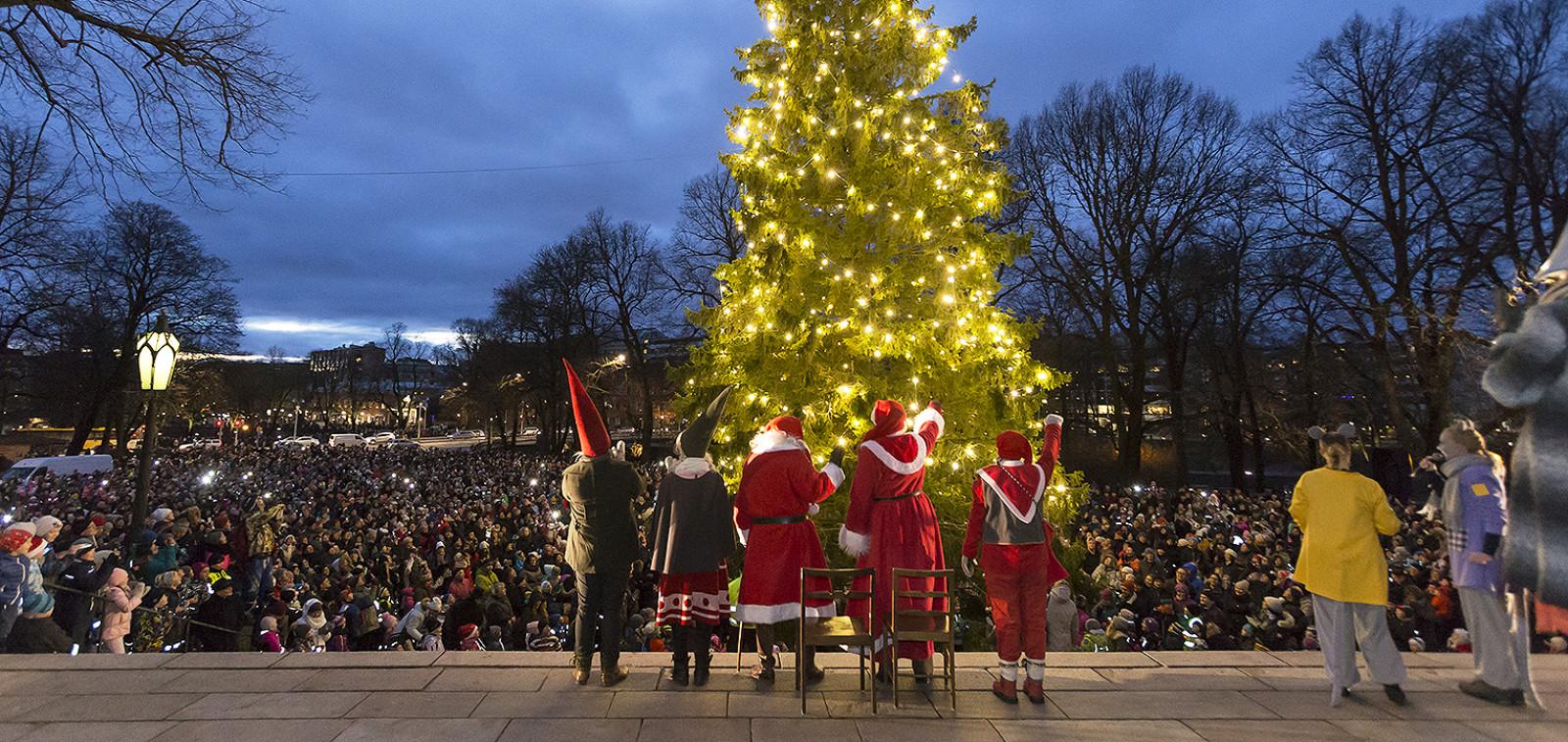Joulupukki joukkoineen heiluttaa yleisölle tuomiokirkon portailla joulukuusen valojen loisteessa