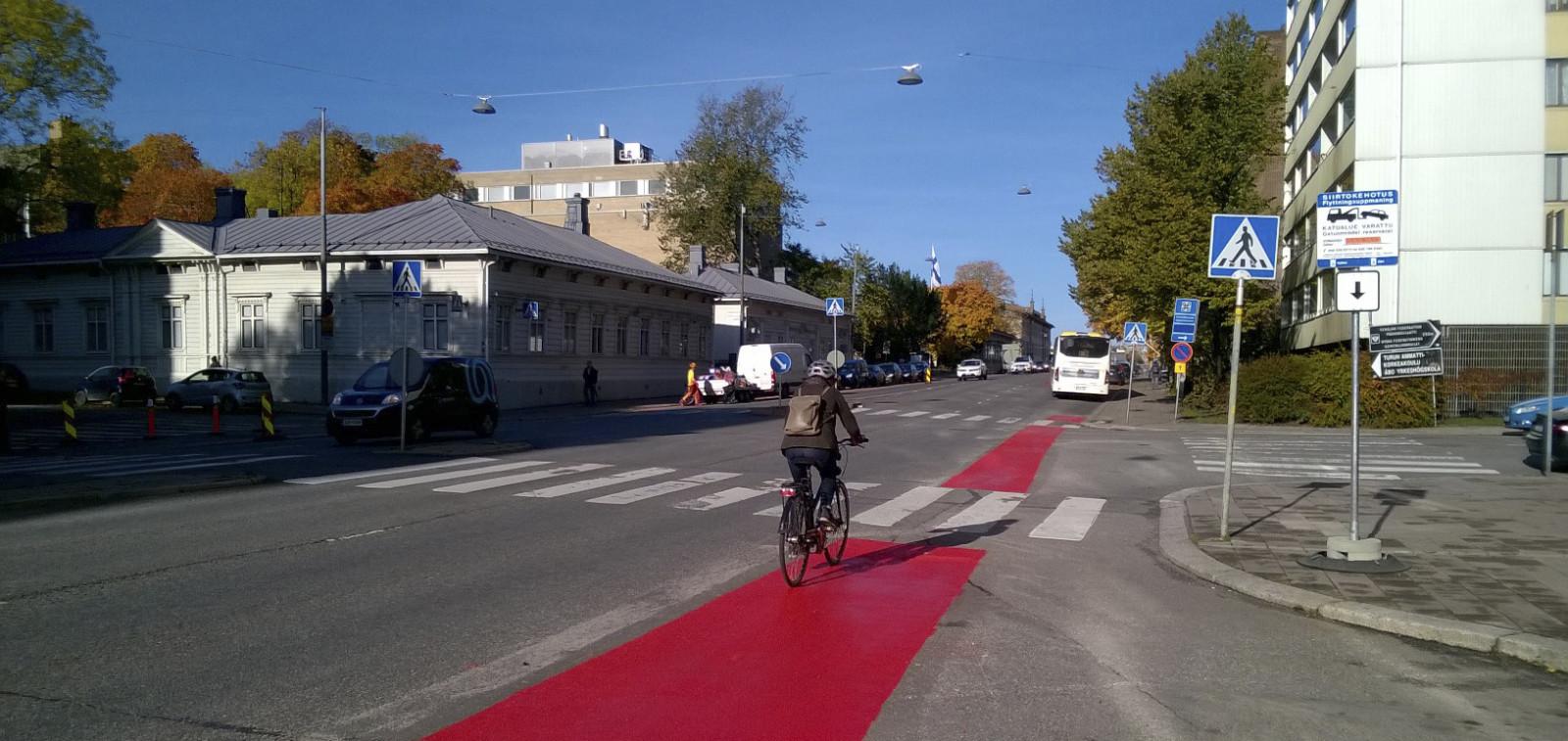 Pyöräilijä ajaa Kaskenkadulla uutta punaista pyöräkaistaa pitkin