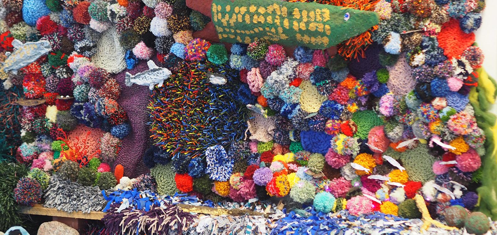 Monenvärisistä villalangoista tehtyjä tupsuja kiinnitettynä seinälle