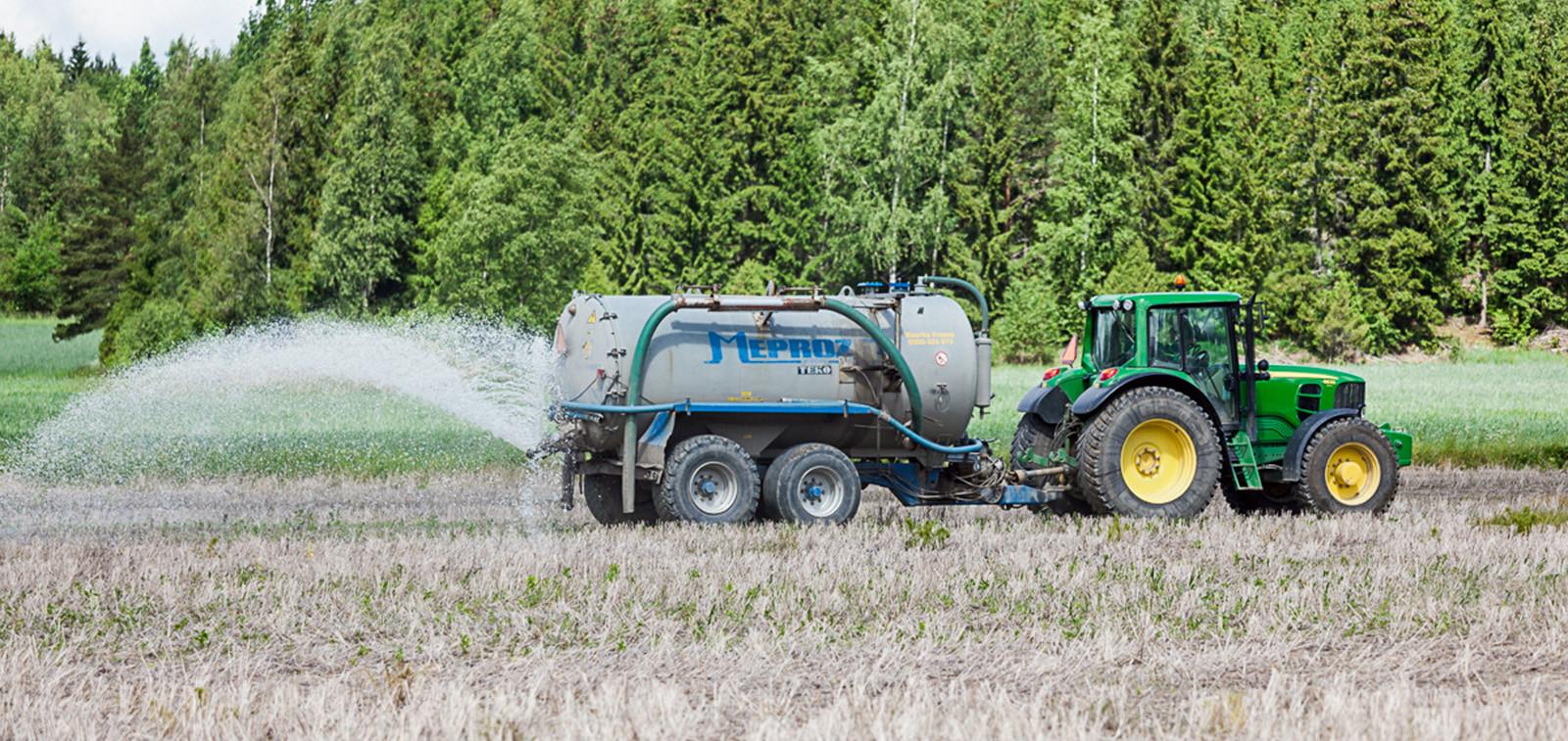 Traktori levittää perävaunusta lietettä pellolle