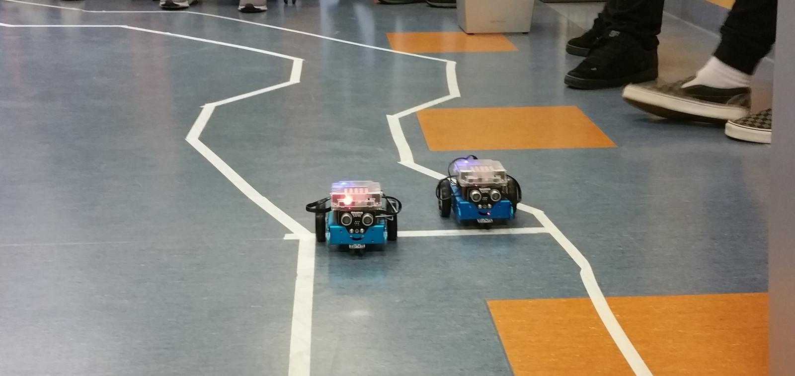 Robottiajokkien kilpa-ajot MyTech päivässä valkoisella teipillä rajatulla lattiaradalla.