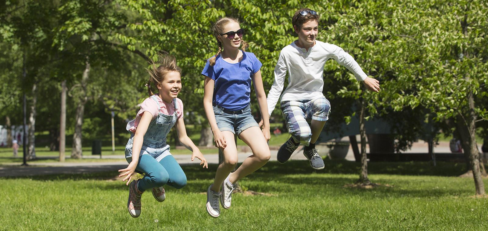 Kolme lasta hyppää ilmaan puistossa