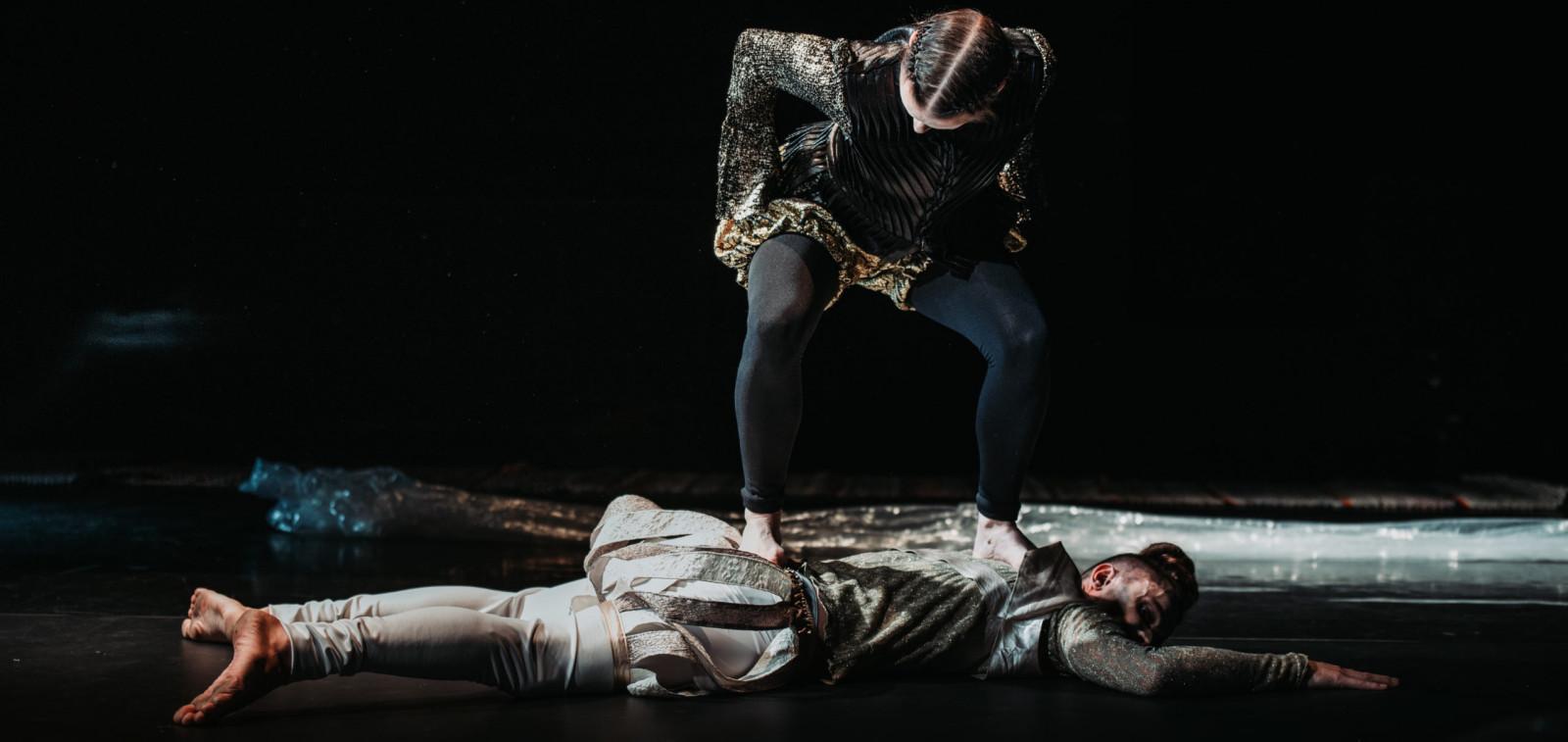 Aurinkobaletin tanssija Côme Calmelet-Pyykkö makaa lattialla ja tanssija Linda Björkqvist seisoo hänen päällään.