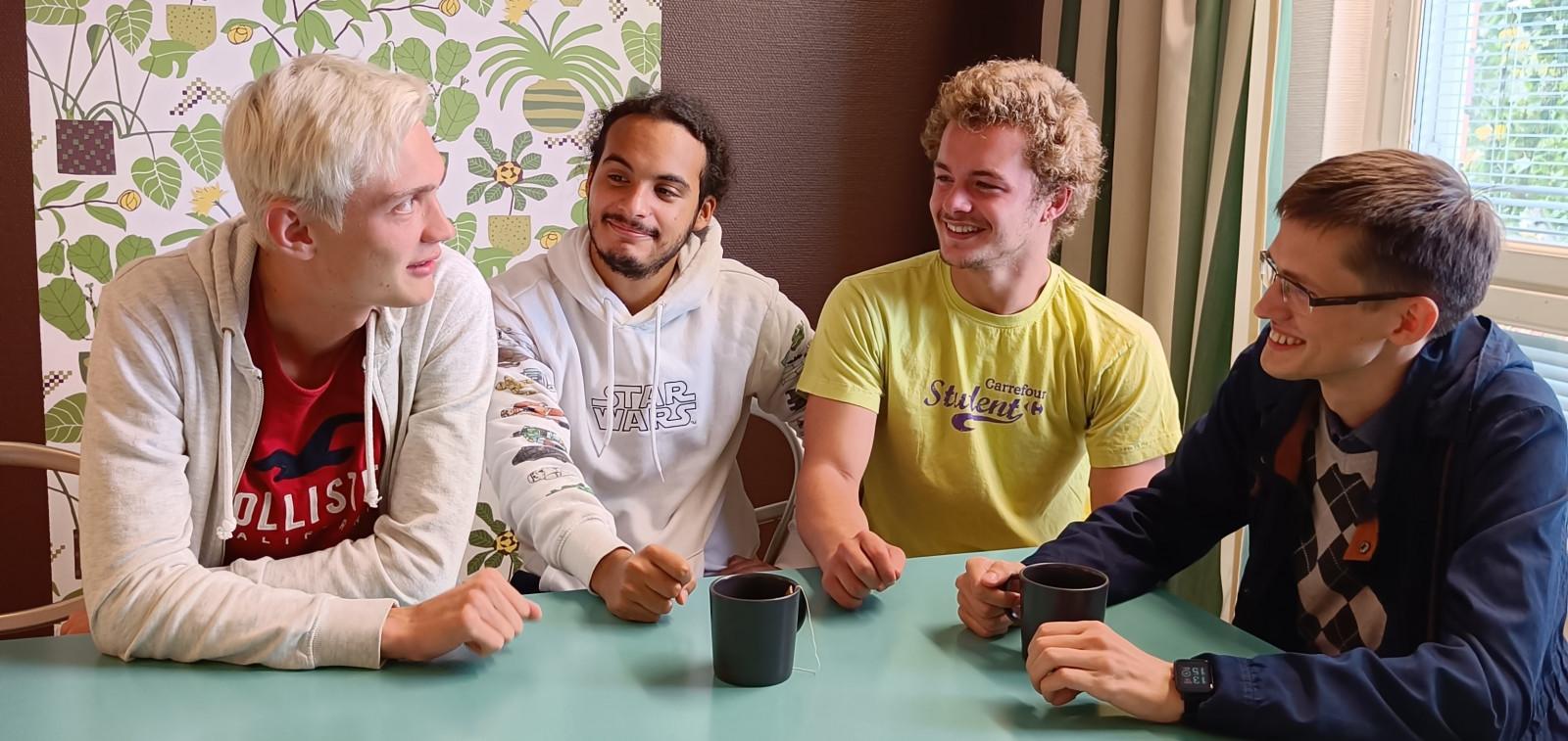 Neljä nuorta miestä istuu pöydän ääressä.