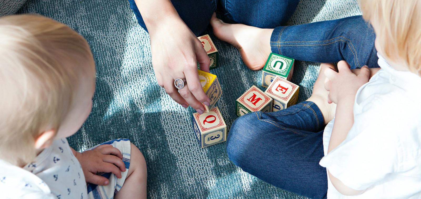 Aikuinen ja kaksi lasta leikkivät rakennuspalikoilla.