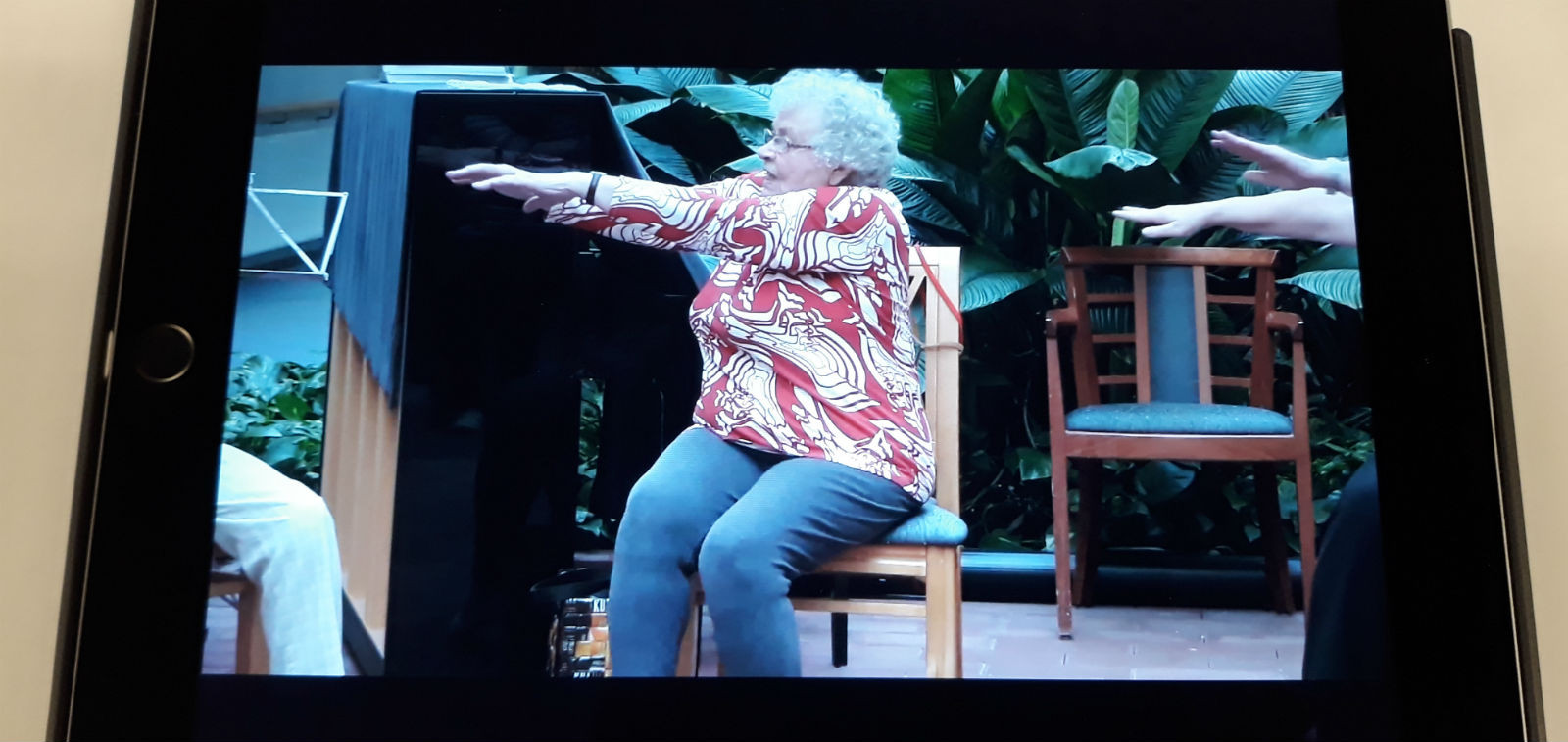 Tabletilla näkyvä video, jossa seniori tekee voimisteluliikettä tuolissa istuen