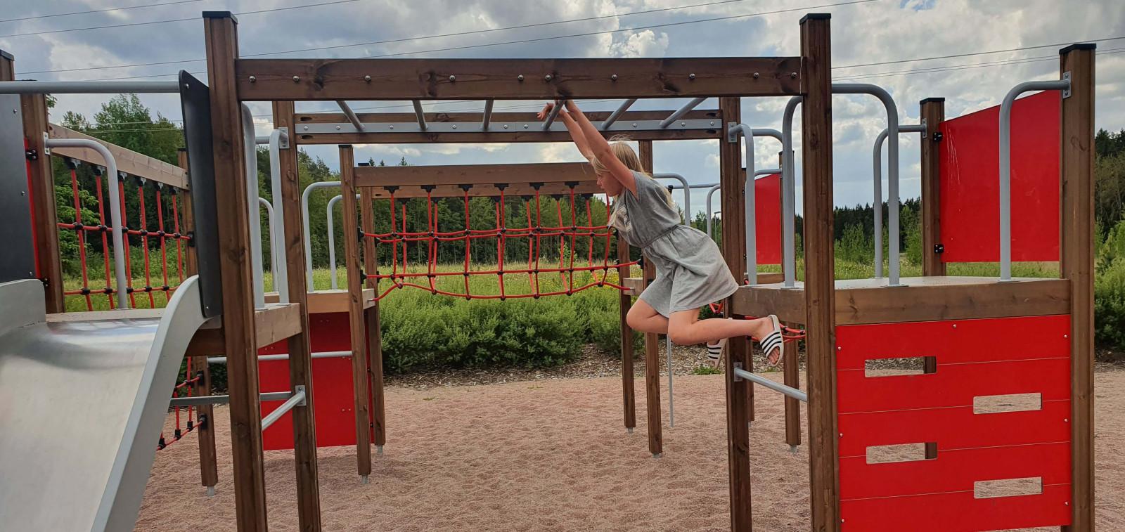 tyttö roikkuu leikkipaikan leikkitelineessä pilvisenä päivänä