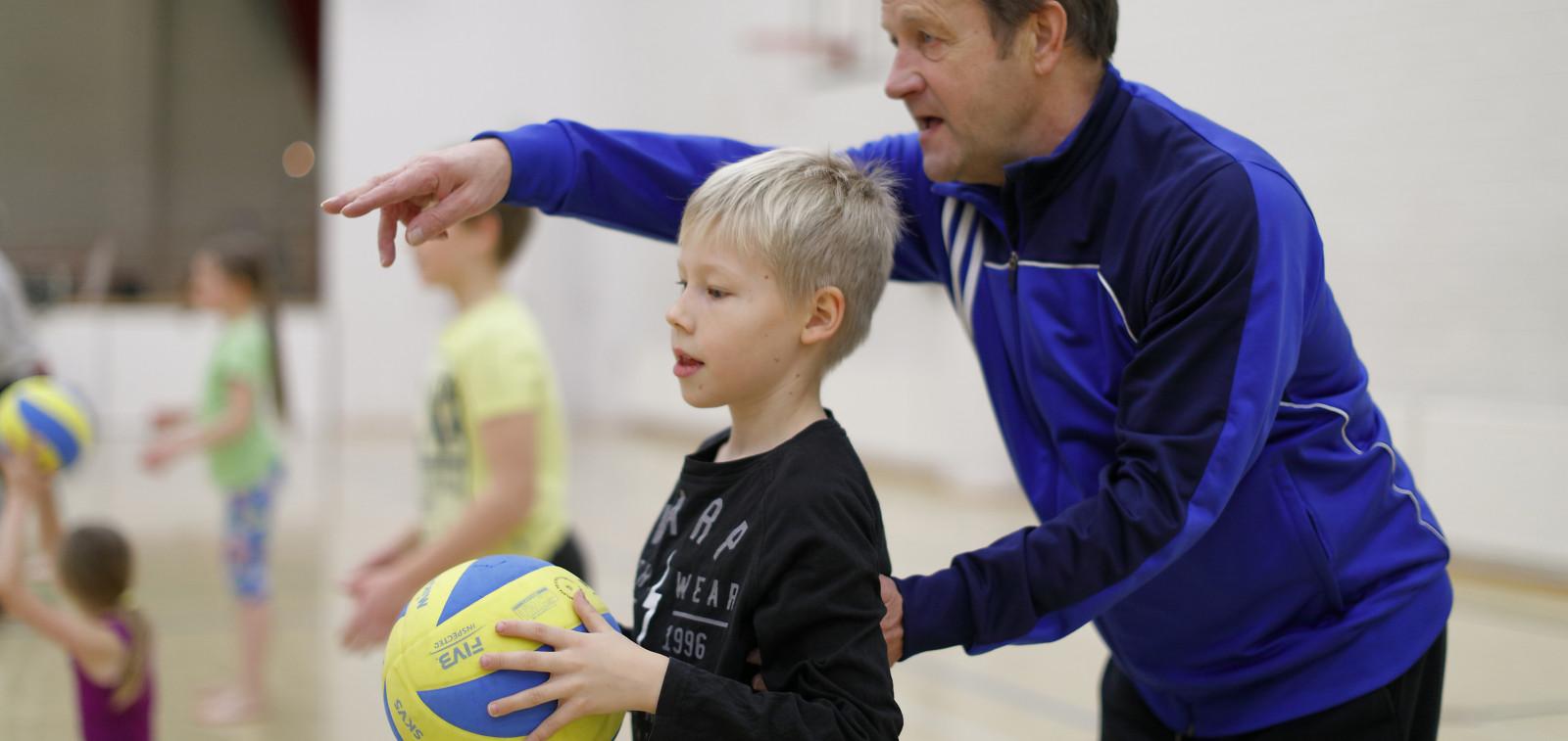 Valmentaja neuvoo poikaa koripalloharjoituksissa.