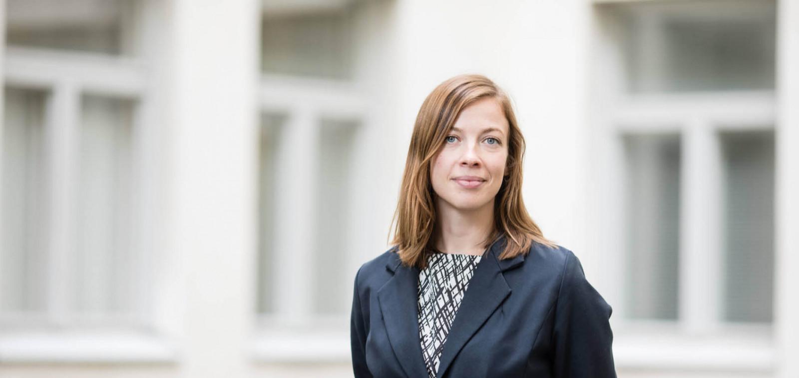 Opetusministeri Li Andersson vaalean rakennuksen edustalla päällään tumma jakkuasu.