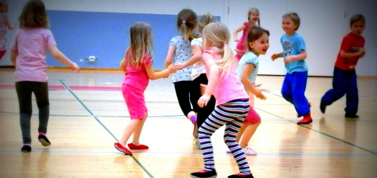 Iloisia lapsia juoksentelemassa liikuntakerhossa