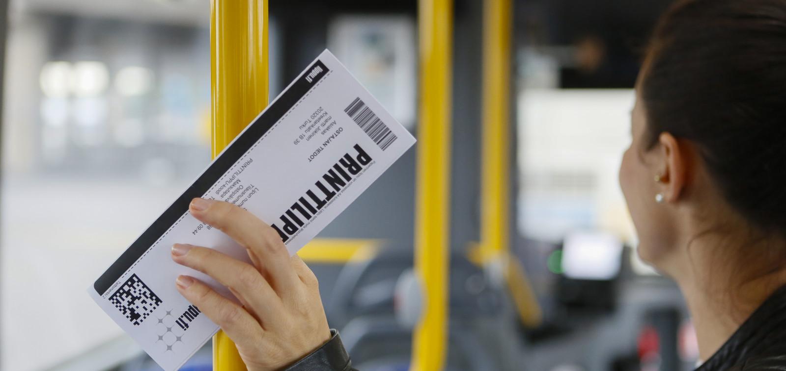 Nainen seisoo teatterilipun kanssa bussissa.