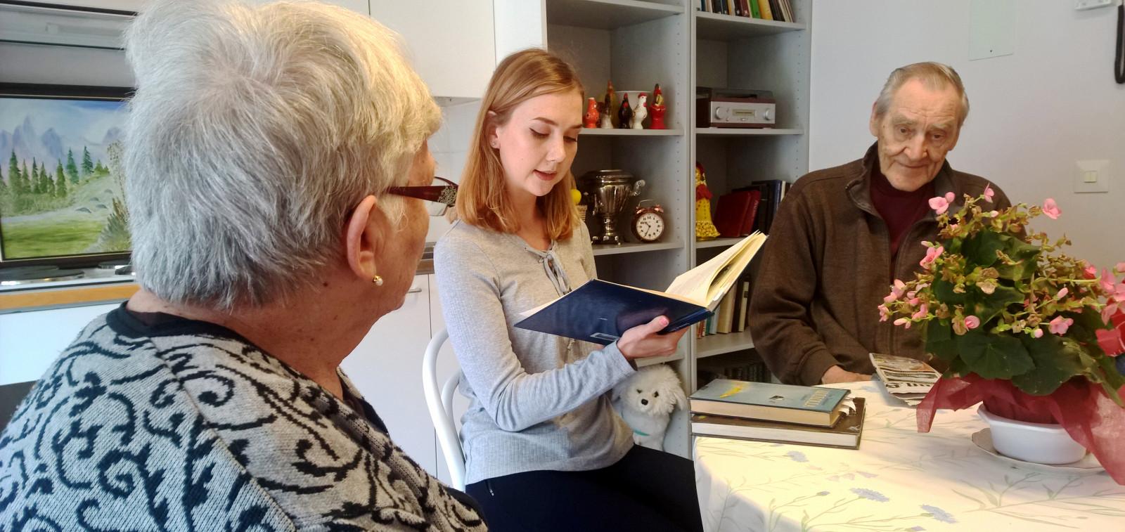 Lukulähetti lukee kirjaa ääneen ikäihmisille