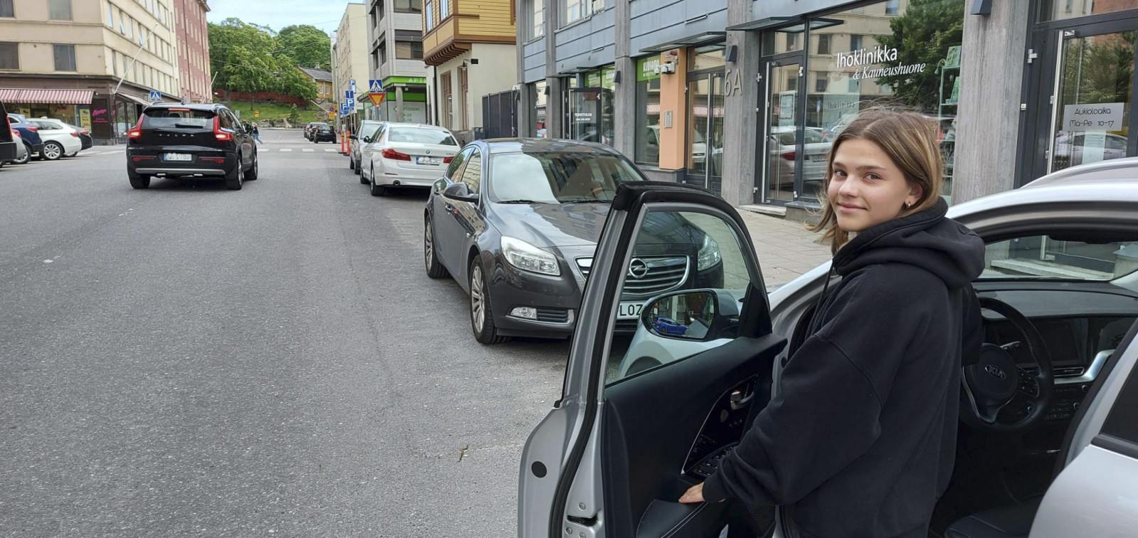 Nainen menossa kadun varteen pysäköityyn autoon