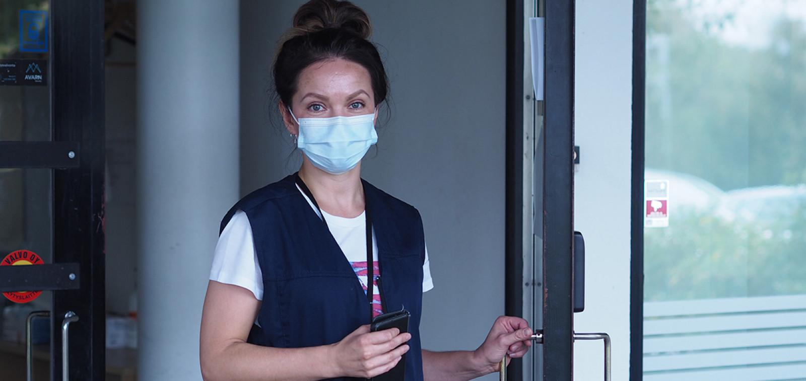 Nainen maski kasvoillaan valkoisessa lyhythihaisessa paidassa pitää kiinni avoimen oven kahvasta