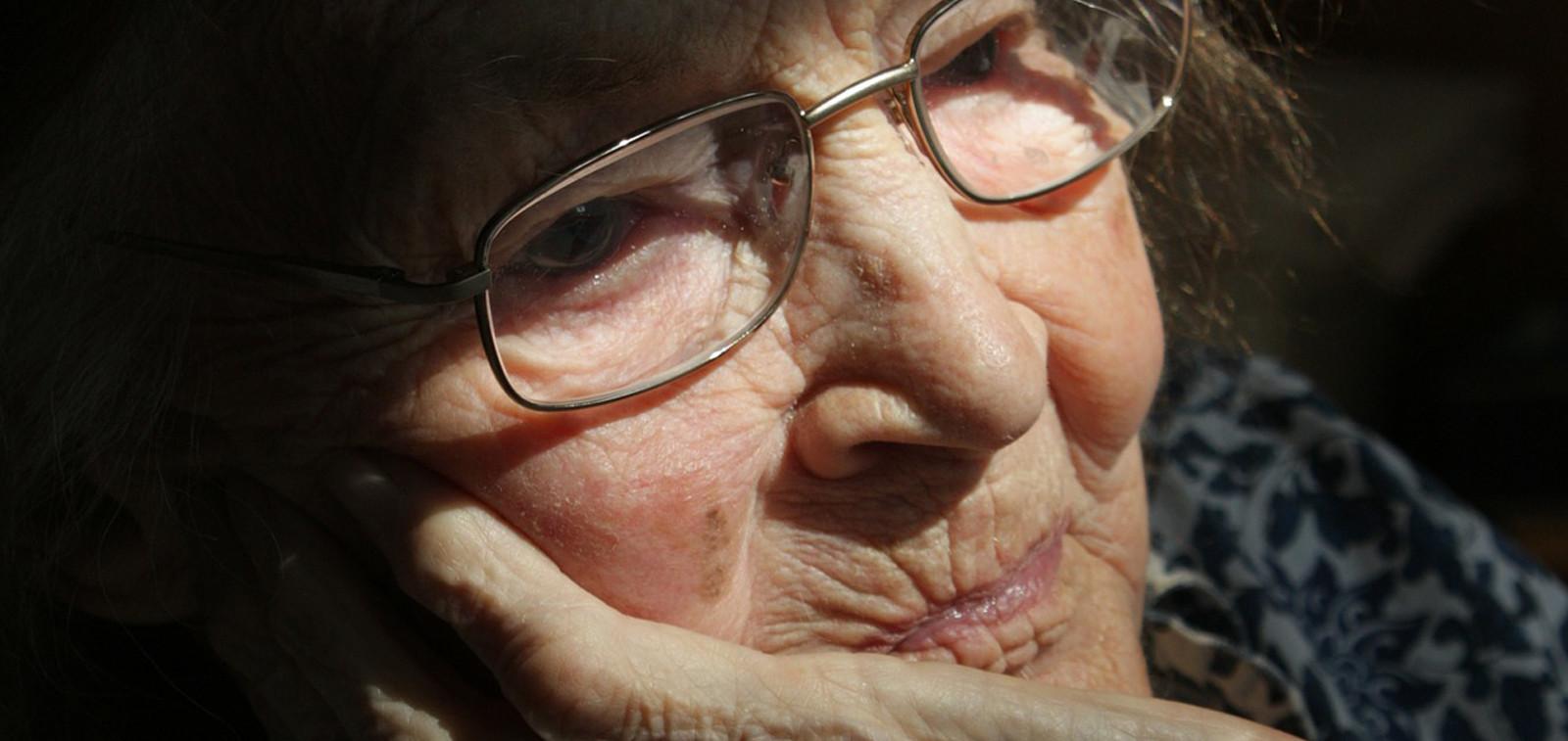 Lähikuvassa iäkäs nainen istuu käsi poskella.