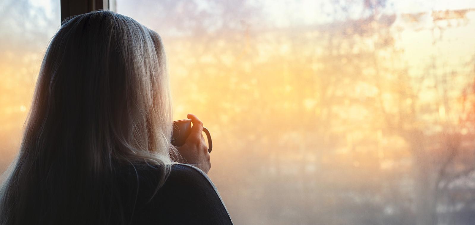 Kahvia juova nainen katsoo ulos ikkunasta.