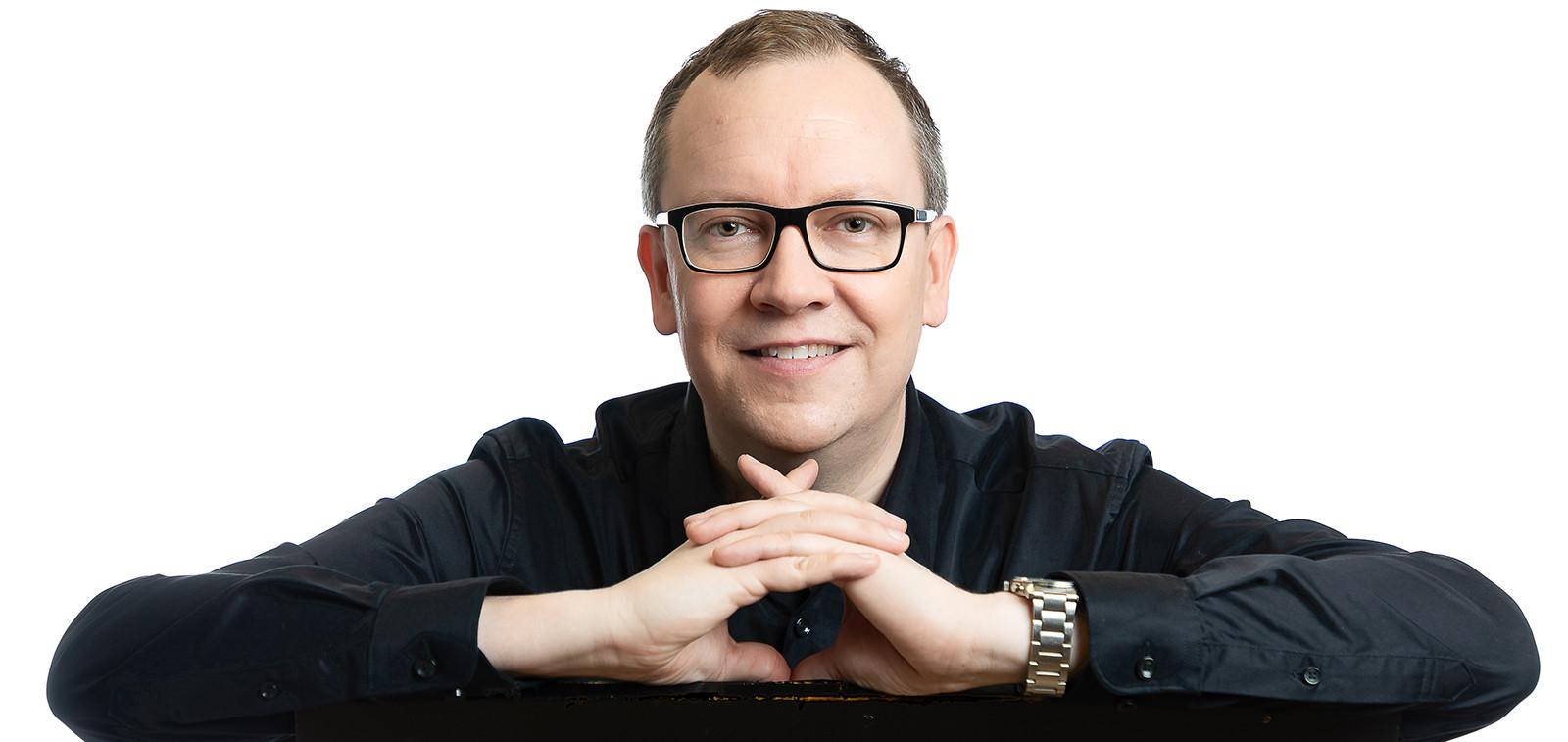 Turun filharmonisen orkesterin intendentti Nikke Isomöttönen katsoo kameraan ja hymyilee.