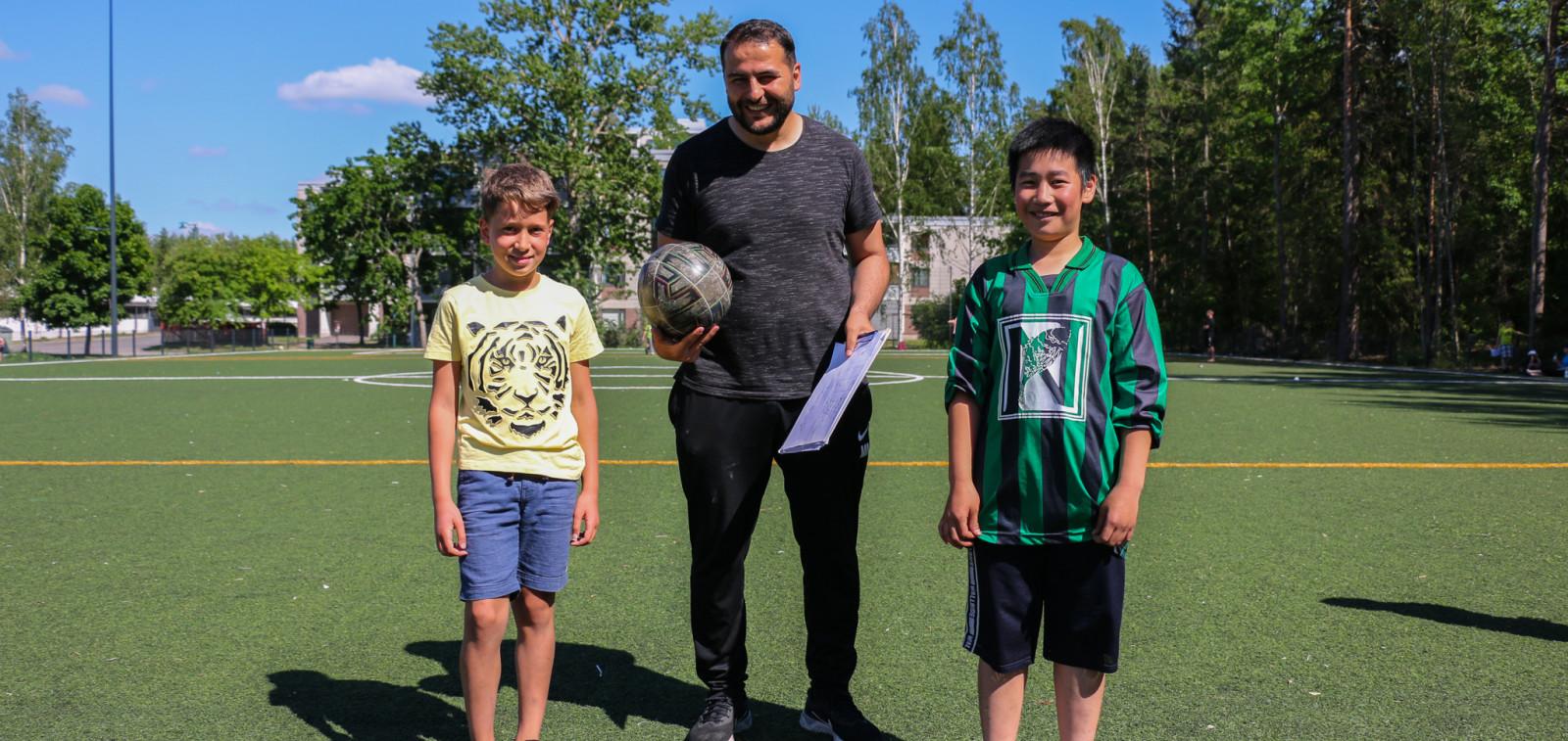 Yksi aikuinen ja kaksi lasta seisovat kesäisellä jalkapallokentällä.