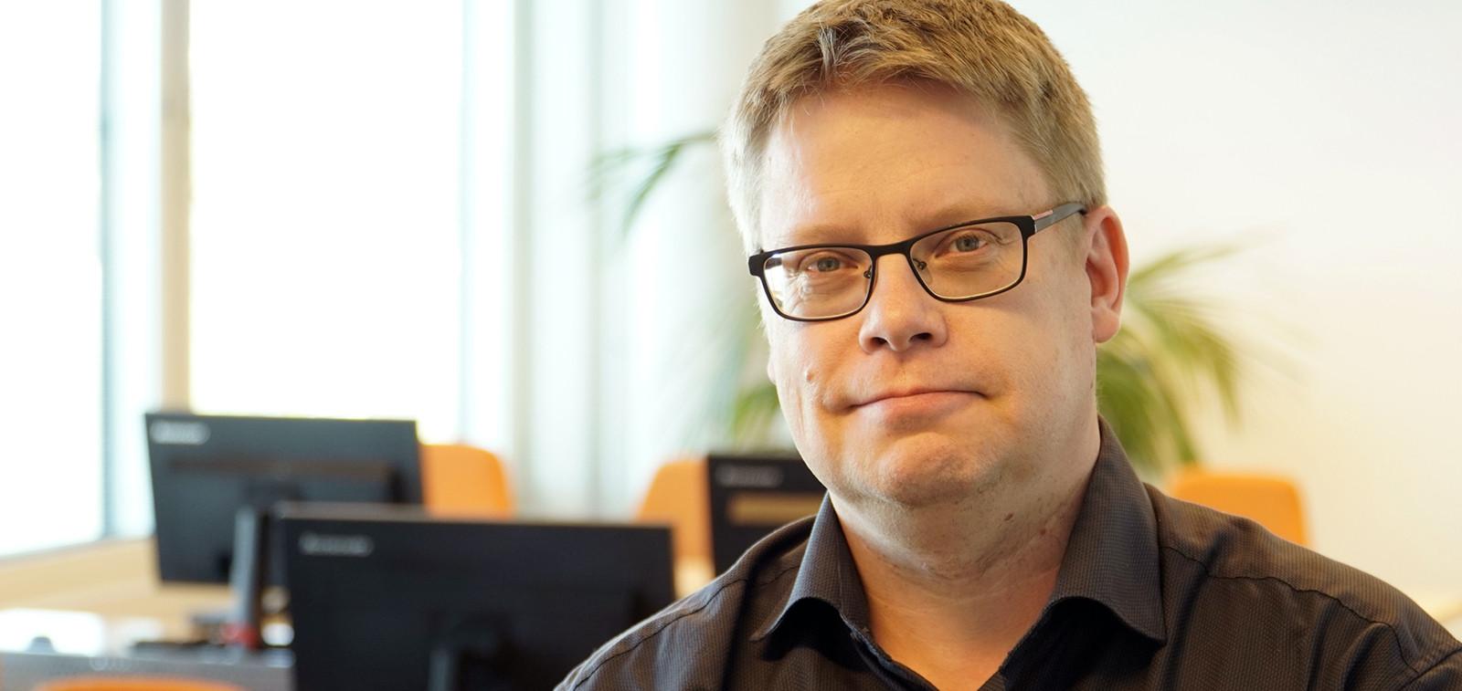 Kuvassa on TOP-keskuksen toiminnanjohtaja Jouni Paakkinen. Kuvassa taustalla näkyy ikkuna, kolme näyttöä ja viherkasvi.