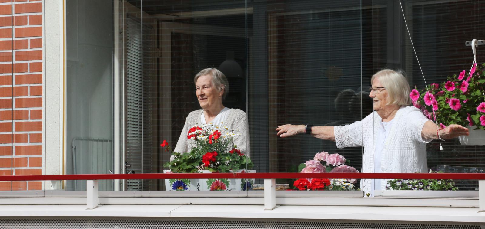 Kaksi vanhaa naista seisovat parvekkeella ja jumppaavat.