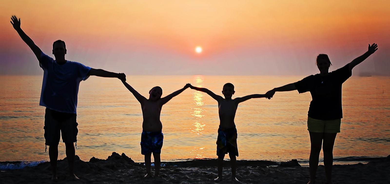 Perhe rannalla auringonlaskun aikaan