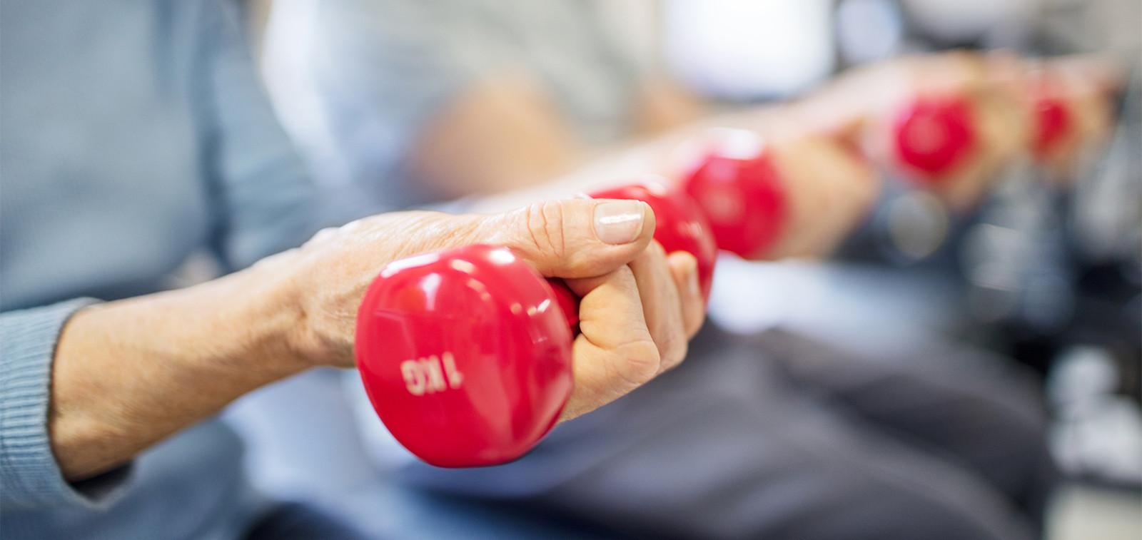 Ikääntyneillä punaiset painot käsissä.