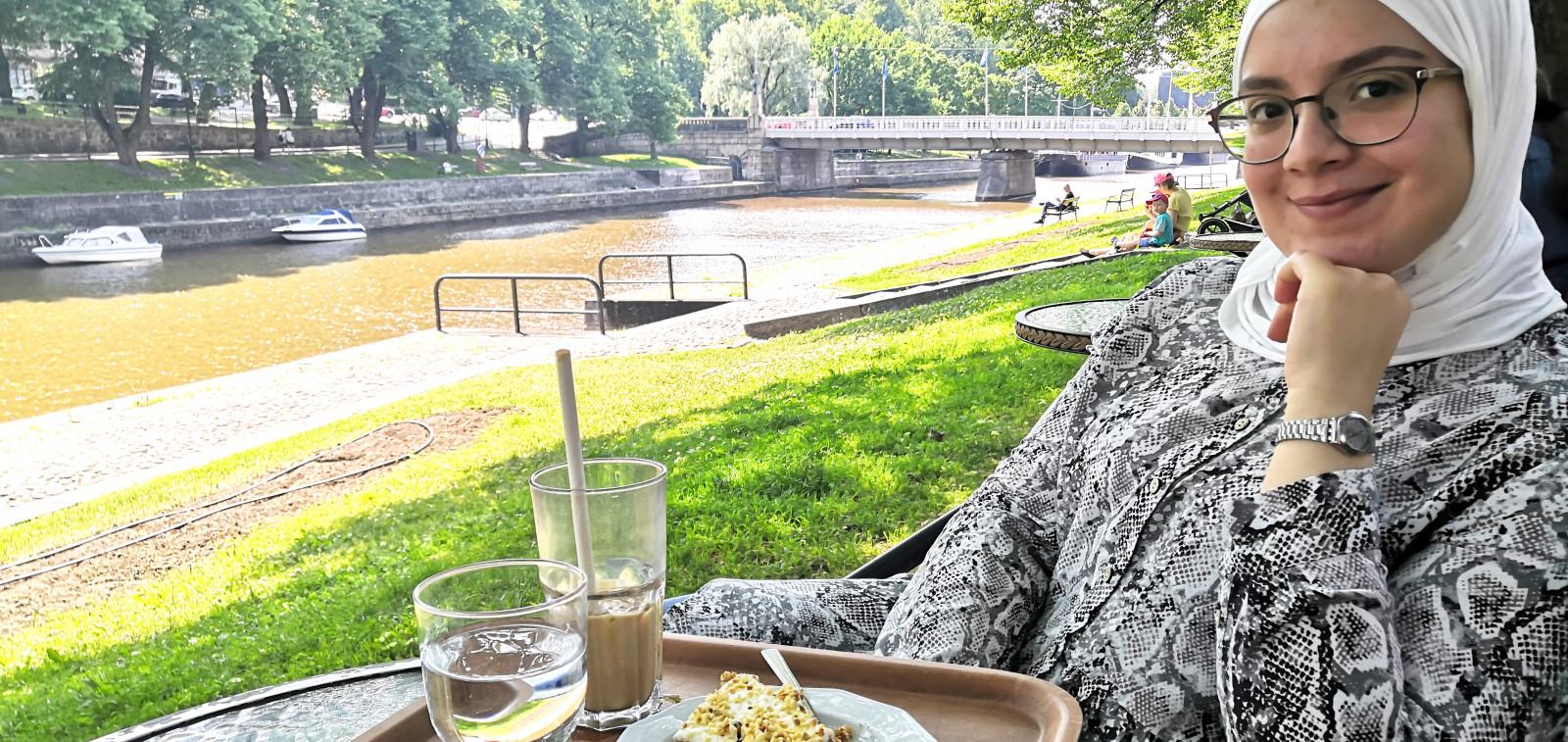 Nuori nainen hymyilee kahvilan ulkopöydässä Aurajoen varrella.