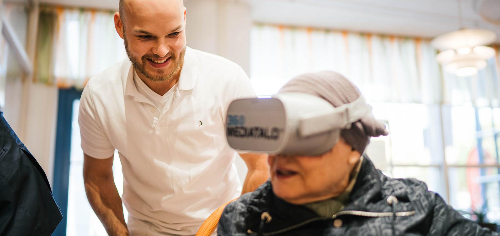 360Mediatalon edustaja ohjaa VR-lasien testaajaa.