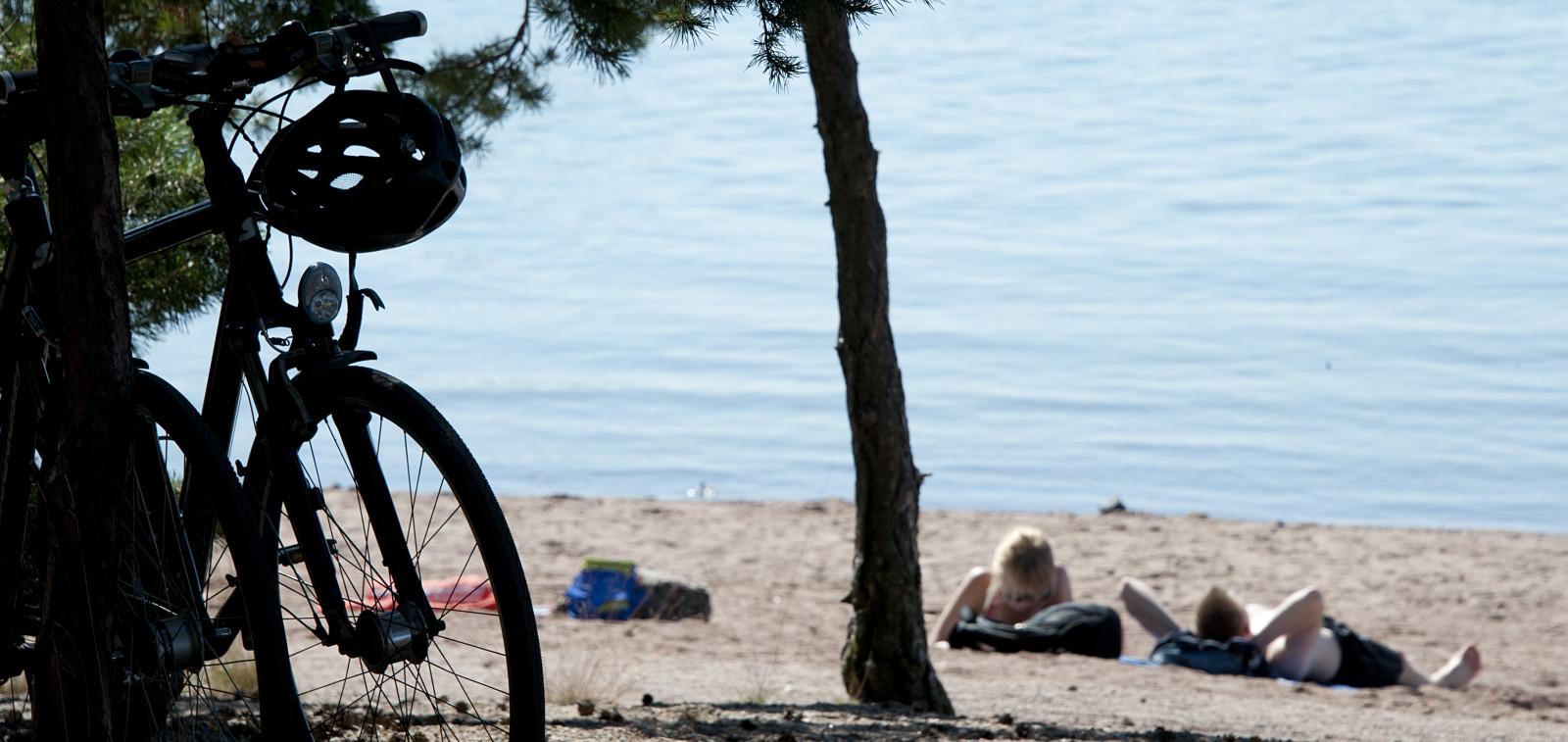 Ihmisiä uimarannalla ottamassa aurinkoa